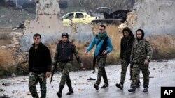 시리아 정부군이 반군을 몰아내고 점령한 알레포 동부에서, 13일 정부군과 친정부군 대원들이 이동하고 있다. 시리아 관영 사나통신이 배포한 사진이다.