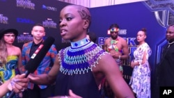 """FILE: Danai Gurira speaks as the cast of """"Black Panther"""" arrives at the South Africa premiere, Feb. 16, 2018, in Johannesburg."""