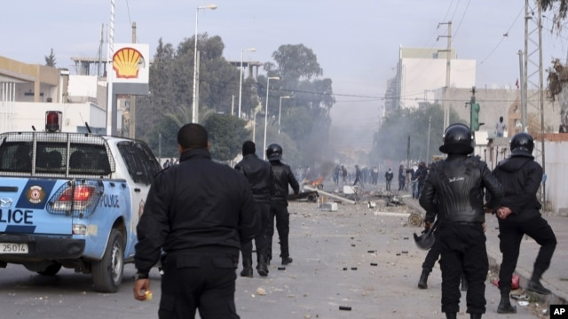 Police forces face protesters in the city of Ennour, near Kasserine, Tunisia, Wednesday, Jan. 20, 2016. Tunisia imposed a nationwide overnight curfew Friday in response to growing unrest as protests over unemployment across the country descended into violence in some cities.