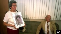 FILE - In this Aug. 9, 2001 file photo, former Guatemalan head of state, Army Gen. Oscar Humberto Mejia Victores, waits to testify as Maria Emilia Garcia, left, holds the photo of her son, union leader Fernando Garcia, at a tribunal in Guatemala City.