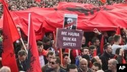 "Kosovo opposition supporters wave Albanian flags during an anti-government rally in Kosovo's capital Pristina, Feb. 17, 2016. The banner in Albanian reads ""Corrupt - with thieves there is no country."""