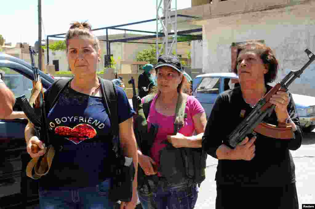 Women with guns are seen in the Christian village of Qaa, where suicide bomb attacks took place Monday, in the Bekaa Valley, Lebanon, June 28, 2016.