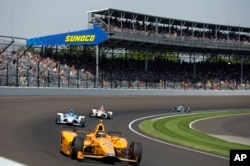 Fernando Alonso, of Spain, leads through the first turn during the final practice session for the Indianapolis 500 auto race at Indianapolis Motor Speedway, May 26, 2017.