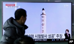 "A man watches a TV news program showing a photo published in North Korea's Rodong Sinmun newspaper of North Korea's ""Pukguksong-2"" missile launch, at Seoul Railway station in Seoul, South Korea, Feb. 13, 2017."