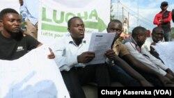 Les jeunes du mouvement citoyen Lutte pour le changement (LUCHA) assis par terre devant le quartier général de la Monusco lisent un mémo, à Goma, Nord-Kivu, RDC, 26 octobre 2017. (VOA/Charly Kasereka)