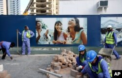 Laborers install paving stones in front of an advertisement for luxury real estate, in the Marina district of Dubai, United Arab Emirates, March 26, 2015.