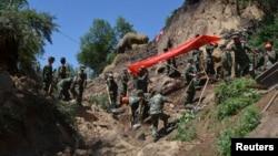 Tentara dan petugas lainnya tengah berupaya melakukan pencarian korban gempa di Dingxi, provinsi Gansu (22/7). Gempa berkekuatan 6.6 SR melanda wilayah ini, Senin pagi (22/7) dan korban tewas hingga saat ini dilaporkan telah mencapai 94 jiwa.