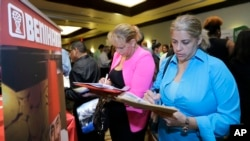 FILE - Job seekers fill out employment applications at a job fair in Miami Lakes, Florida.