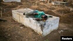 Un creuseur de tombes de victimes d'Ebola se repose dans un cimetière de Freetown, le 17 décembre 2014. (Reuters/Baz Ratner)