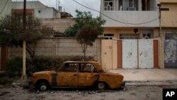 Un automóvil dañado permanece en una calle de un barrio recientemente liberado por fuerzas de seguridad iraquíes de militantes islámicos en el oeste de Mosul, Irak, el sábado 18 de marzo de 2017.