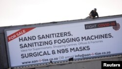 A worker attaches a billboard, advertising sales of hand sanitizer and masks, to a building ahead of a 21 day lockdown aimed at limiting the spread of coronavirus disease (COVID-19), in Cape Town, South Africa, March 25, 2020. Reuters/ Mike…