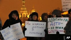 "Opposition activists hold posters reading ""Do not involve children in politics"" and ""Lawmakers, children are not your ownership"" during a protest against a bill banning U.S. adoptions of Russian children in St. Petersburg, Russia, December 26, 2012."