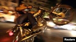 一名埃及總統穆爾西的支持者星期一在開羅解放廣場上騎著摩托車﹐慶祝穆爾西下令埃及國會恢復議事