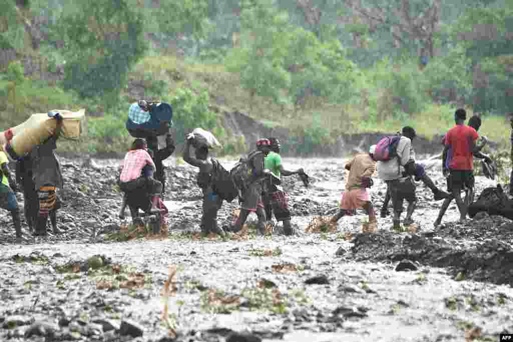 People cross the river La Digue in Petit Goave, where the bridge collapsed during the rains from Hurricane Matthew, southwest of Port-au-Prince, Haiti, Oct. 5, 2016.