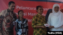 Menteri Sosial RI Dra. Khofifah Indar Parawansa (baju putih) didampingi walikota Solo, F.X. Hadi Rudyatmo (baju batik) membagikan kartu elektronik e-Warong bagi warga miskin di Solo (Foto: VOA/Yudha)