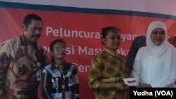 Menteri Sosial Khofifah Indar Parawansa (kanan) didampingi walikota Solo, F.X. Hadi Rudyatmo (kiri) membagikan kartu elektronik e-warong bagi warga miskin di Solo. (Foto: Dok)