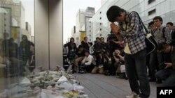 Sinh viên Takashi Udagawa, 15 tuổi, cầu nguyện khi đặt hoa để tưởng nhớ Steve Jobs trước một cửa hàng Apple trong quận Ginza ở Tokyo, ngày 6/10/2011