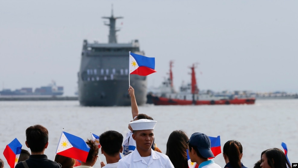 FILE - Relatives of crew of BRP Tarlac of the Philippine Navy wave Philippine flags to welcome its arrival at the South Harbor in Manila, Philippines, May 16, 2016. The radars Manila is purchasing from the U.S. will be mounted on Navy ships.