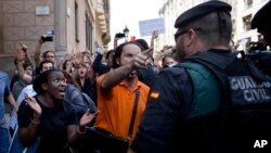Demonstrators react as they try to stop the car carrying Xavier Puig, a senior at the Department of External Affairs, Institutional Relations and Transparency of the Catalan Government office, after he was arrested by Guardia Civil officers in Barcelona, Spain, Sept. 20, 2017.