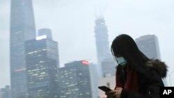 بیجنگ میں دھوئیں اور گرد و غبار سے بچنے کے لیے ایک خاتون نے ماسک پہن رکھا ہے۔ چین میں فضائی آلودگی کی بڑی وجہ کارخانوں کا دھواں ہے۔ فائل فوٹو