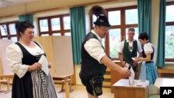 Warga Jerman mengikuti pemilihan umum legislatif dengan mengenakan pakaian tradisional Bavaria di sebuah TPS di Hornberg-Reichenbach,Jerman (22/9).