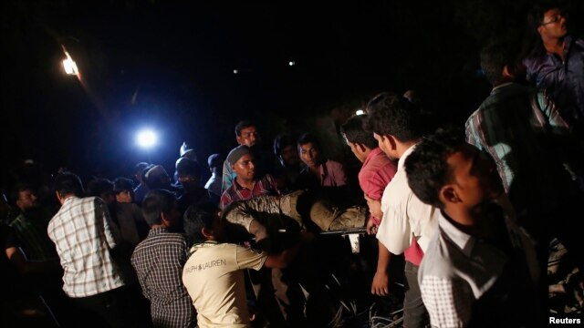 Rescue workers carry a body from a collapsed residential building in Thane, on the outskirts of Mumbai, April 4, 2013.