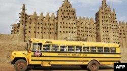Un bus du ministère de l'Education passe devant la Grande Mosquée de Djenné dans la région du Delta du Niger au centre du Mali, 9 février 2005.