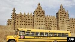 Un bus du ministère de l'Education passe devant la Grande Mosquée de Djenné dans la région du Delta du Niger au centre du Mali, le 9 février 2005.