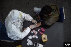 Seorang petugas kesehatan (kiri) mengambil sampel darah dari seorang pengendara motor yang melanggar Pembatasan Sosial Berskala Besar (PSBB) di sebuah kantor polisi di Surabaya, 3 Mei 2020. (Foto: AFP)