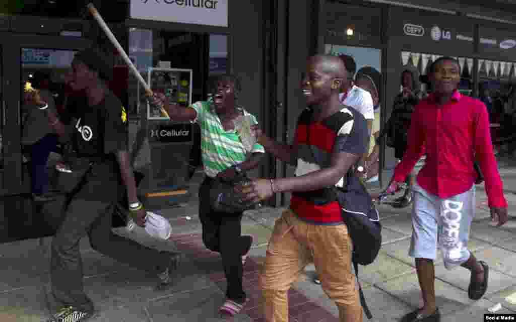 Grupo marchando com armas improvisadas pelas ruas.