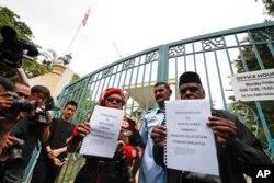 24일 쿠알라룸푸르 주재 북한 대사관 앞에서 말레이시아 시민단체 관계자들이 김정남 암살 사건과 관련해 북한 정부에 항의하는 서한을 들고 있다.