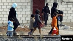 Cư dân từ thị trấn Ras al-Ain ở miền bắc Syria vượt biên giới vào Thổ Nhĩ Kỳ, ngày 13/11/2012.
