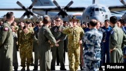 An official yells to members of aircrews, who are involved in the search for missing Malaysia Airlines plane MH370, to get them into position for an official photograph as they stand on the tarmac at the Royal Australian Air Force (RAAF) Pearce Base, Apri