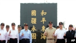 """Taiwan's President Ma Ying-jeou, fifth from left, poses for a group photo in front of a monument reading: """"Peace in the East China Sea and our national territory secure forever"""" during his visit to Pengjia Islet in the East China Sea, north of Taiwan, April 9, 2016."""