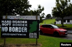 "FILE - A car drives past a sign saying ""No Border, Hard border, soft border, no border"" in Londonderry, Northern Ireland, Aug. 16, 2017."