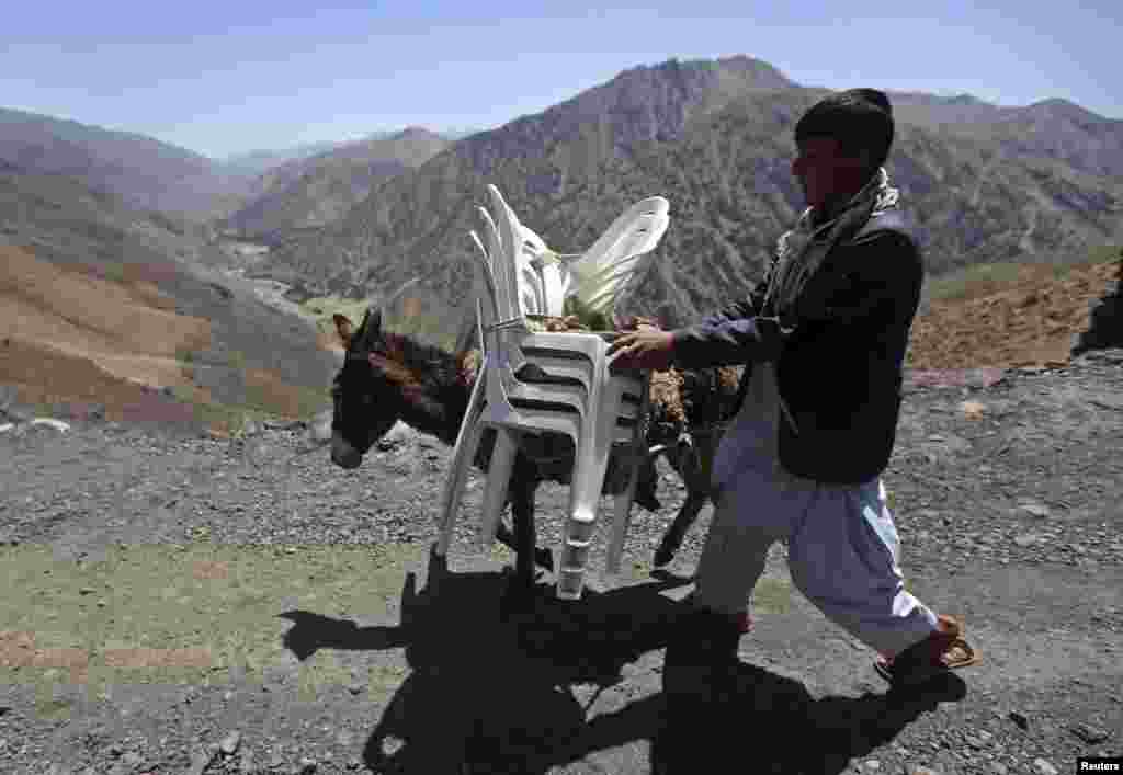 A man walks with a donkey loaded with ballot boxes and other election material to be transported to polling stations not accessible by road in Shutul, Panjshir province, June 13, 2014.