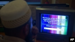 FILE - A Pakistani viewer looks at a television screen flashing suspension notice of GEO News channel in Islamabad, Pakistan.