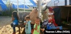 Suhu yang panas di dalam tenda membuat dua orang ibu dan anak-anak mereka beraktifitas di luar tenda pada siang hari, 18 Juni 2019.(Foto: Yoanes Litha/VOA)