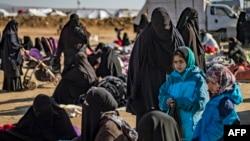 Para ibu dan anak-anak duduk-duduk di kamp al-Hol, tempat pengungsian keluarga mantan kombatan ISIS, di wilayah al-Hasakeh, timur laut Suriah, 14 Januari 2020. (Foto: AFP)