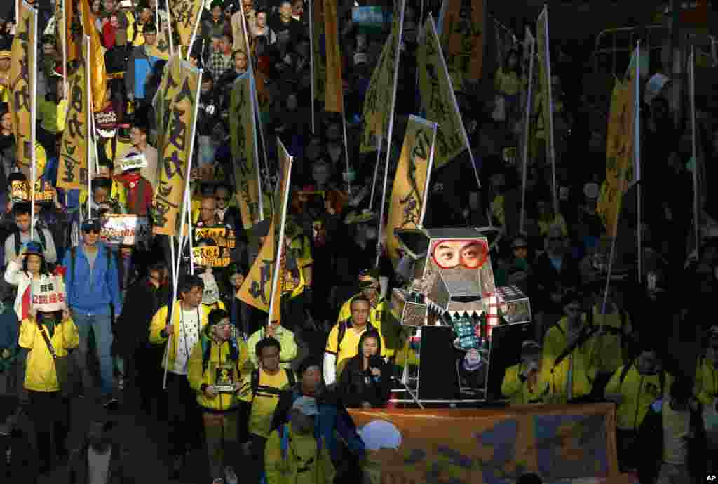 Protesters carry an effigy of a wolf representing Hong Kong's Chief Executive Leung Chun-ying march during a demonstration in Hong Kong, Jan. 1, 2014.