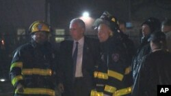 Republican presidential candidate Indiana Gov. Mike Pence talks with firefighters at New York's LaGuardia Airport after his campaign plane slid off the runway while landing, Oct. 27, 2016.
