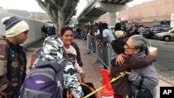 Luz Bertila Zazueta, de 75 años, de Tijuana, (derecha), se despide de una familia peruana cuyos número fueron llamados el 26 de septiembre de 2019 para reclamar asilo en San Diego, California, EE.UU.