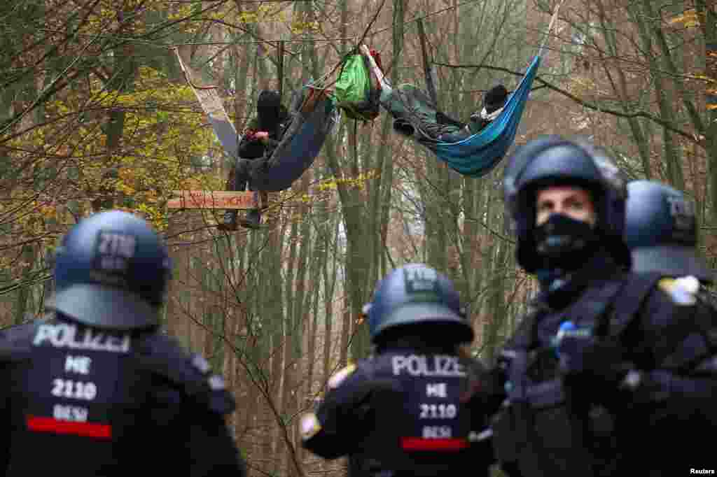 Police officers are seen as demonstrators lie in hammocks hanging from trees during a protest against the extension of the A49 motorway, in a forest near Stadtallendorf, Germany.