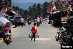 FILE - A man carries eggs as he crosses a street at a Sepaku market in North Penajam Paser regency, East Kalimantan province, Indonesia, Aug. 29, 2019.