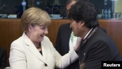 German Chancellor Angela Merkel greets Bolivian President Evo Morales at a European Union-Community of Latin American and Caribbean States summit in Brussels, June 10, 2015.