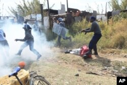 Armed Zimbabwean police battle rioters in Harare, Monday, July, 4, 2016.