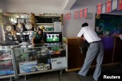 一名朝鲜妇女在平壤一家商店等候顾客。(2013年7月29日)