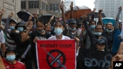 Anti-coup protesters flash the three-finger salute and chant slogan during the demonstration against the military coup in the rain at Pabedan township in Yangon, Myanmar, Friday, April 30, 2021. (AP Photo/Vincent Thian)