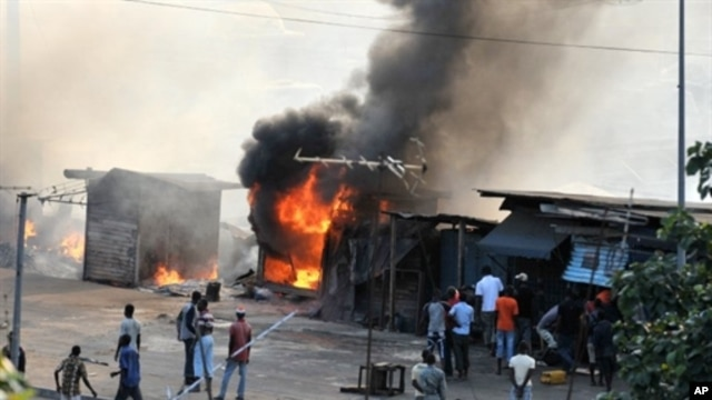 People stand next to stores set on fire during clashes between supporters of Alassane Dramane Ouattara and soldiers of the FDS, loyal to outgoing president Laurent Gbagbo, in the Attecoube neighborhood, in Abidjan on February 24, 2011.