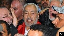 Rachid Ghannouchi (au centre) à son arrivée à l'aéroport international de Tunis, le 30 janvier 2011